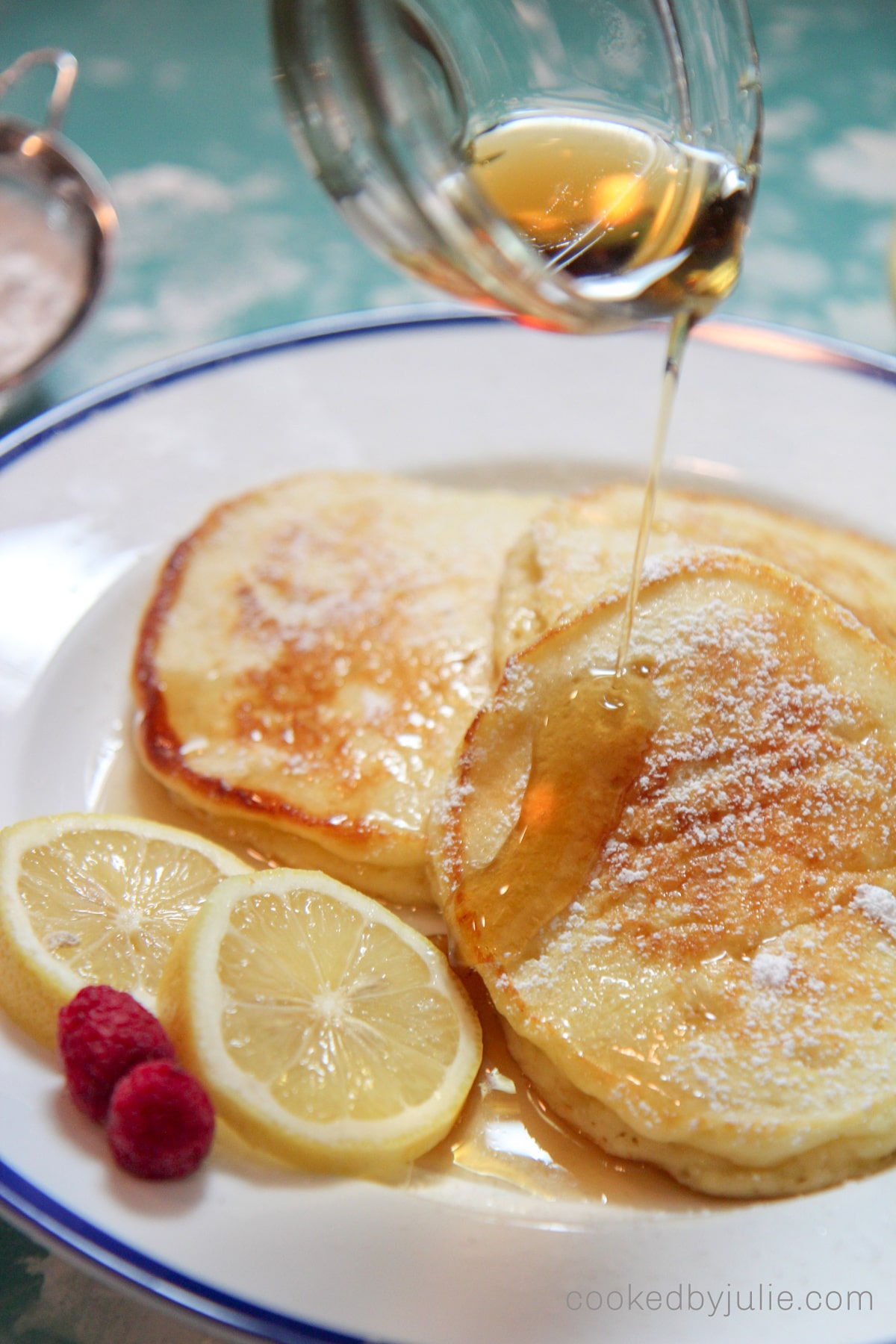 three lemon ricotta pancakes on a white and blue plate with syrup drizzled over it, two lemon slices, and two raspberries on the side.