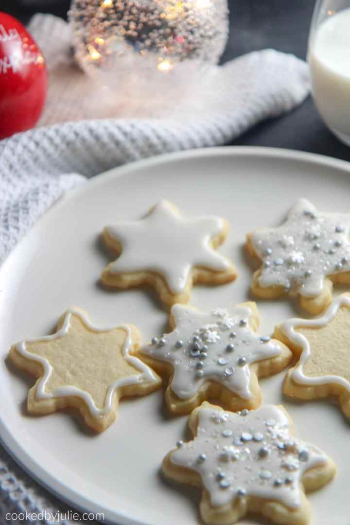 six cookies on a white plate with a white towel on the side, a glass of milk, and two Christmas tree balls on the side.