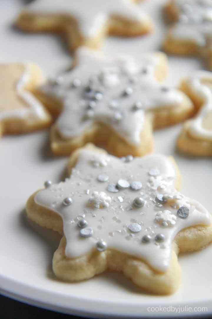 six cut out sugar cookies on a white plate.