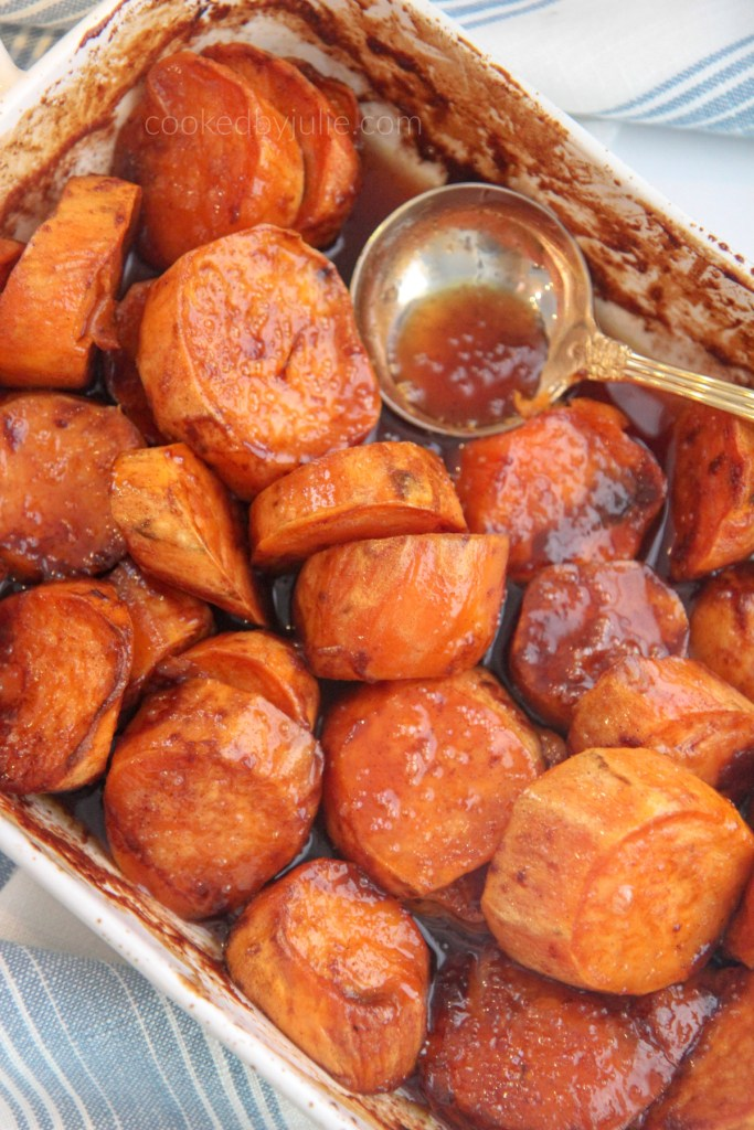 baked candied yams in a white baking dish and gold spoon