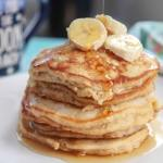 banana pancakes on a white plate with fresh banana and syrup