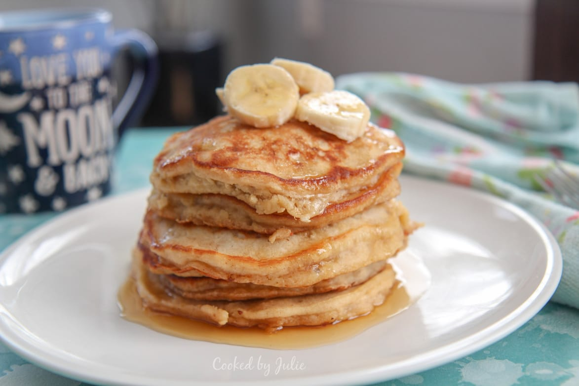 a stack of banana pancakes with maple syrup and banana slices on top