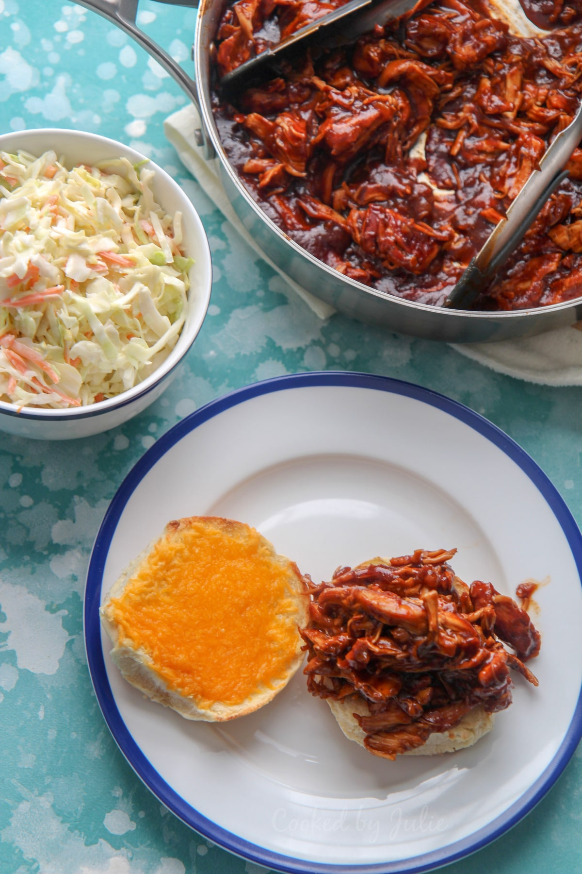 pulled chicken sandwich with cheddar cheese on a white and blue plate. Coleslaw in a bowl and pulled chicken in a skillet