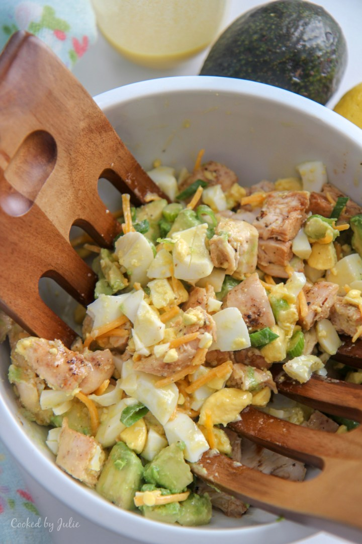 avocado chicken salad in a white bowl and wooden salad mixers