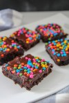 brownies with rainbow chips on top of a white plate