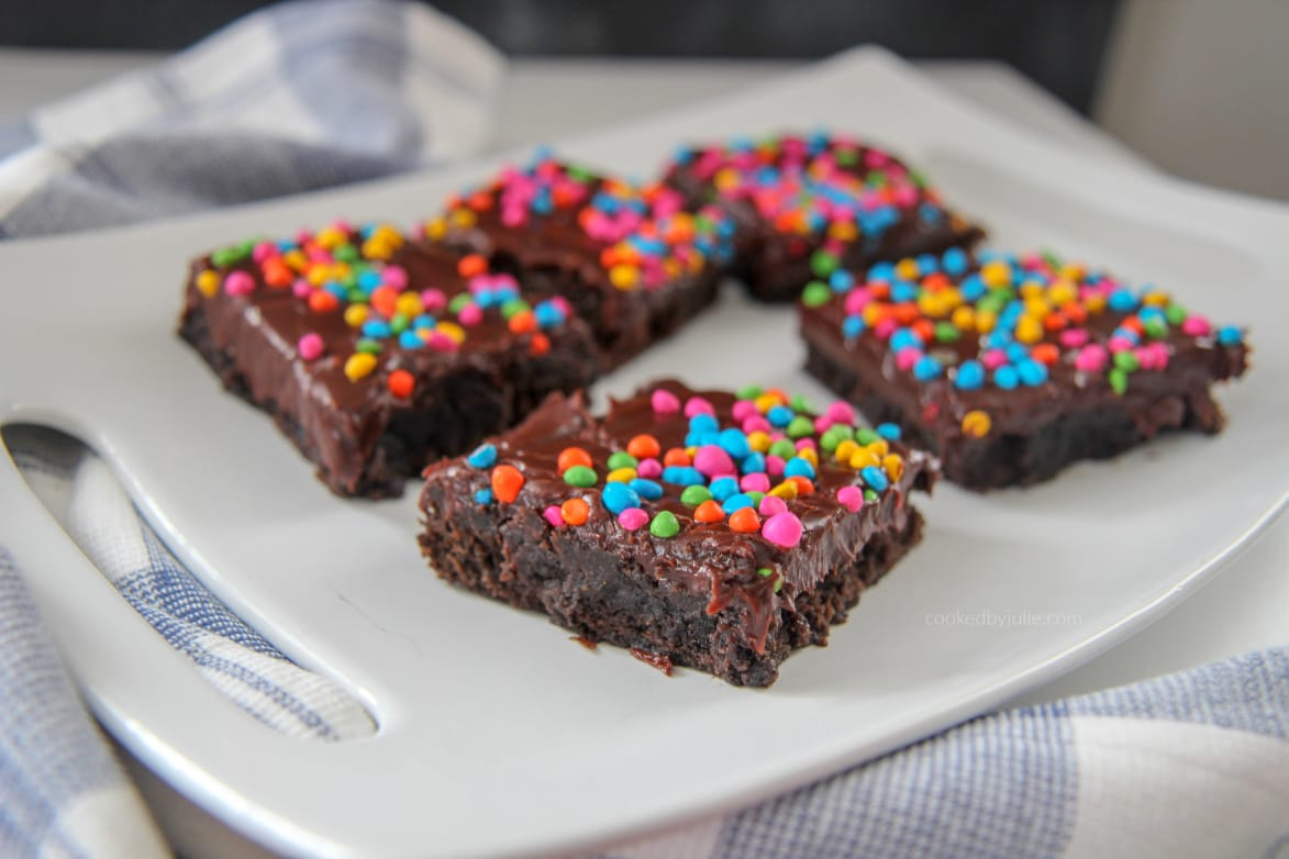 cosmic brownies on a white plate with a blue and white towel on the side