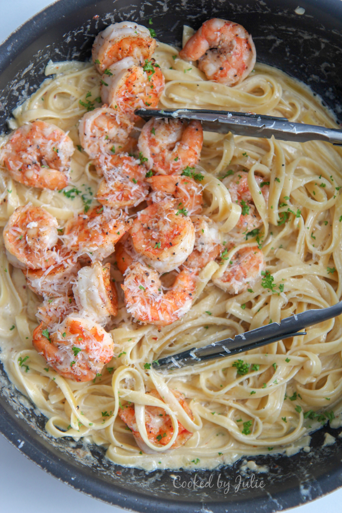 shrimp over fettuccine alfredo in a black skillet with tongs and fresh parsley