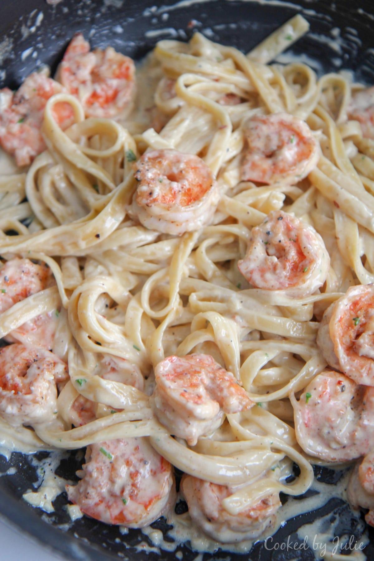 shrimp and fettuccine alfredo tossed in a black skillet