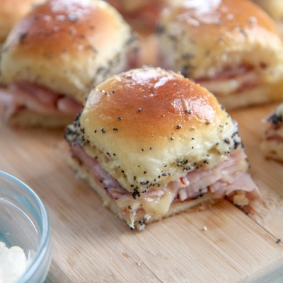 ham and cheese sliders on a wooden board with mayo on the side