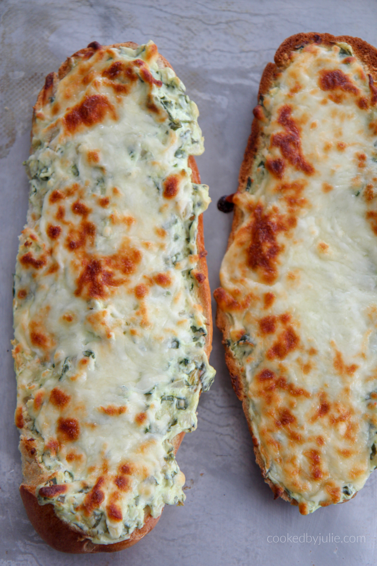 two loafs of cheesy spinach artichoke bread on a baking sheet