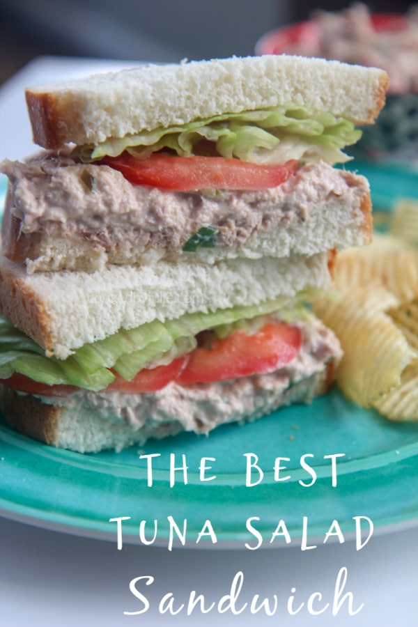 tuna salad sandwiches stacked on a blue plate with potato chips
