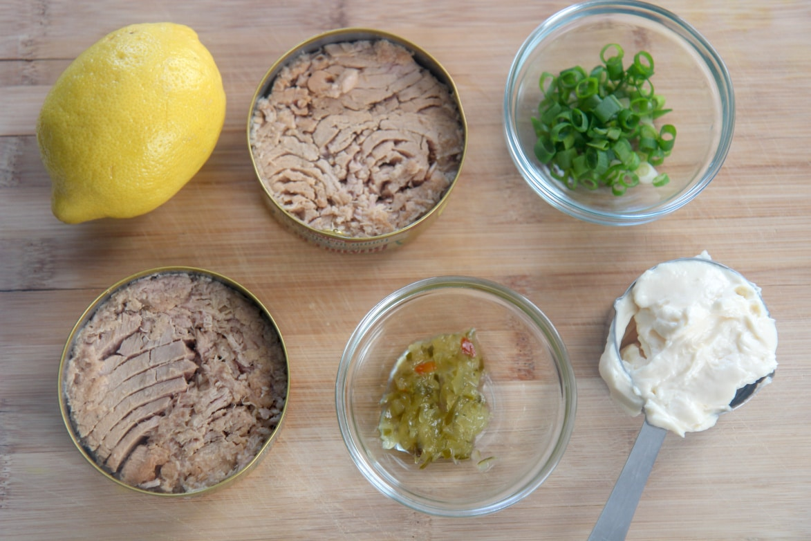 canned tuna, lemon, sweet relish, mayo, and scallions in small bowls on a wooden board