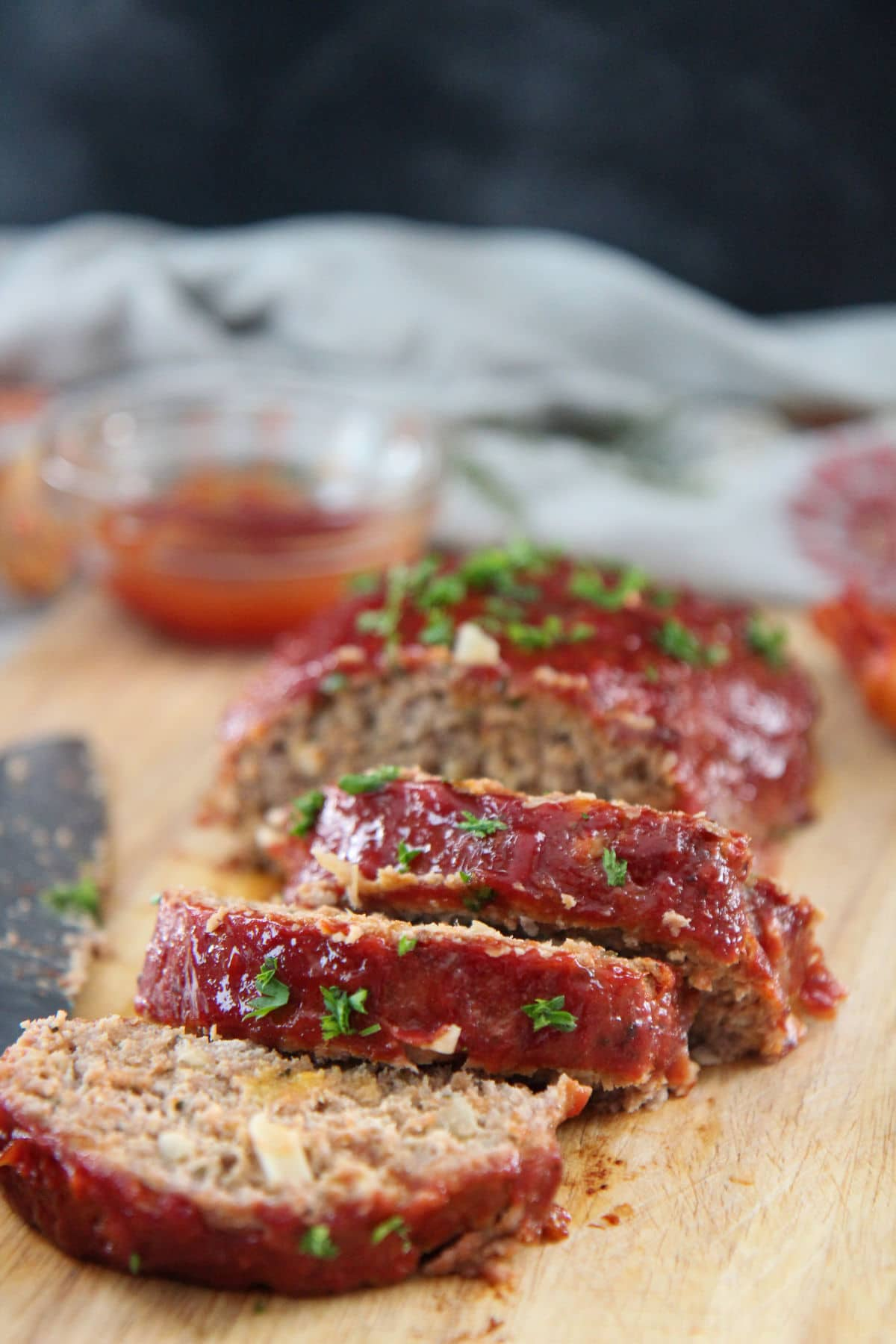 slices of turkey meatloaf on a wooden board with ketchup on the side
