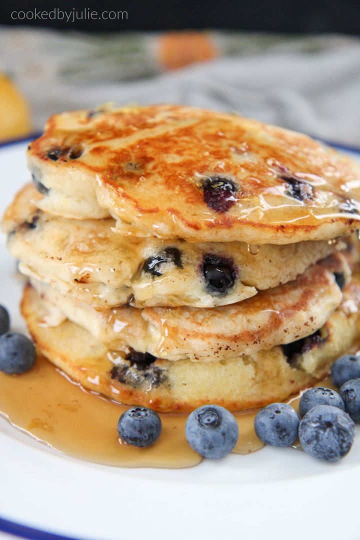stacked pancakes with syrup and blueberries on the side
