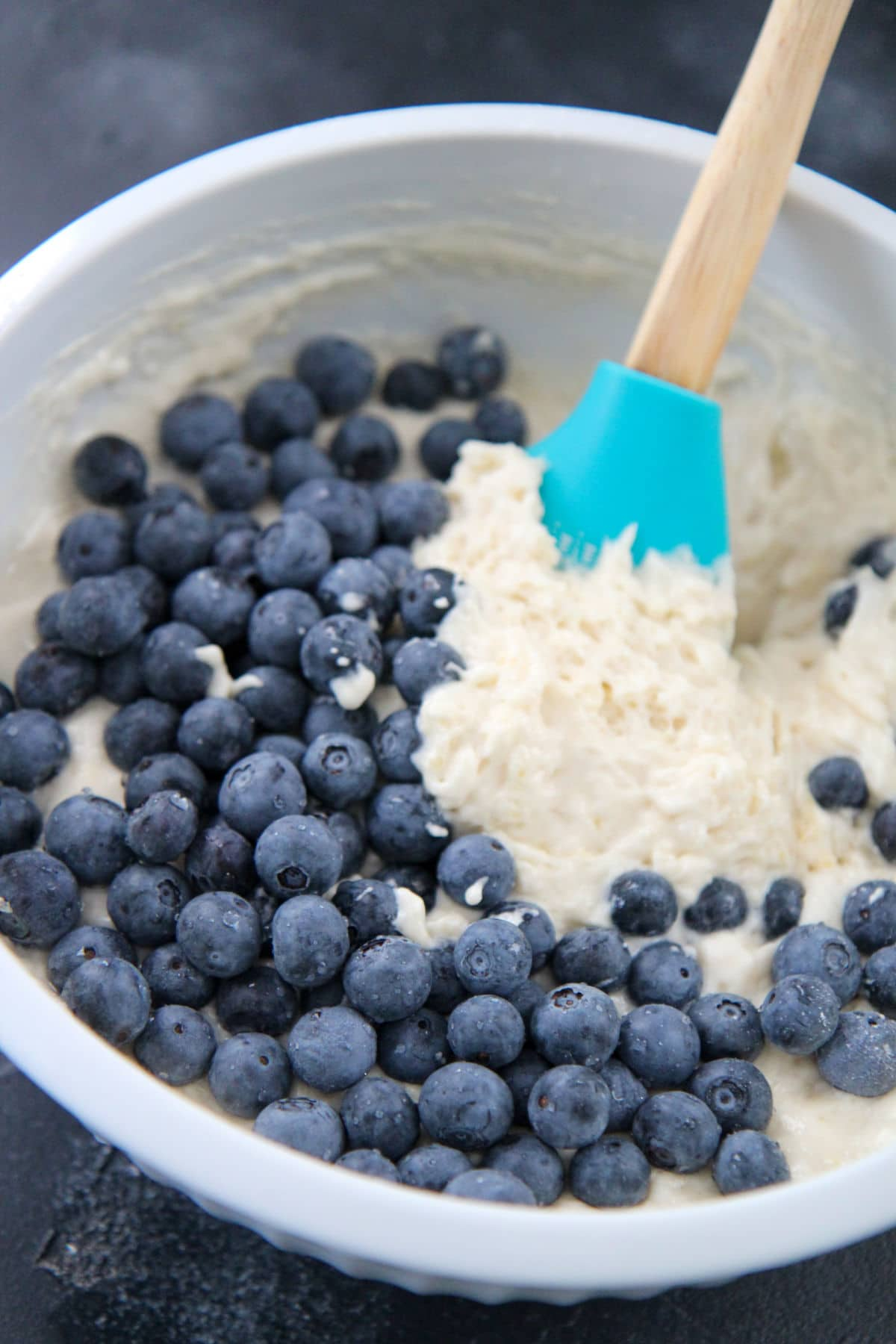 pancake batter with blueberries on the side and a spatula in a bowl