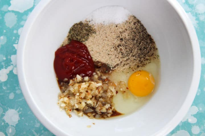 egg, ketchup, onions, seasonings, and breadcrumbs in a white bowl