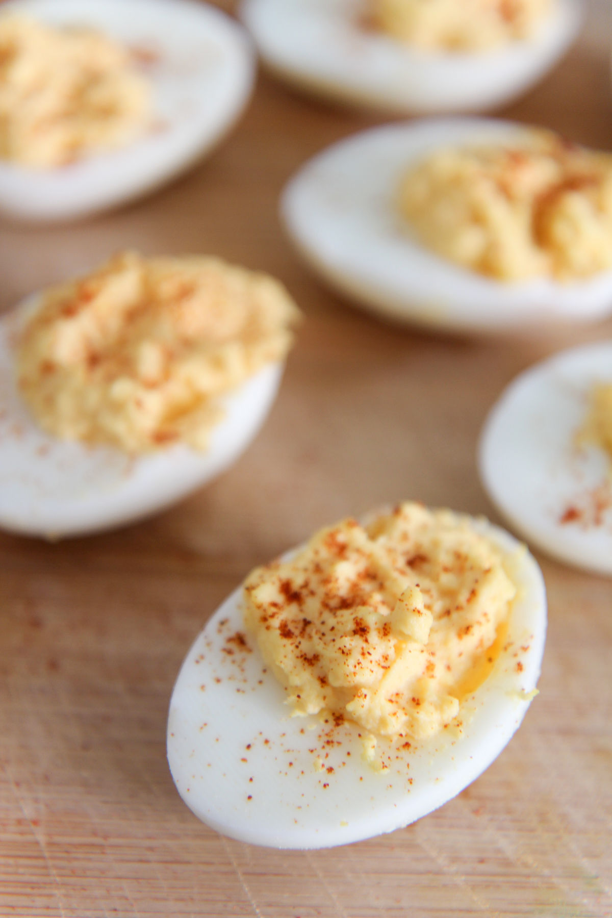 deviled eggs with paprika on a wooden board