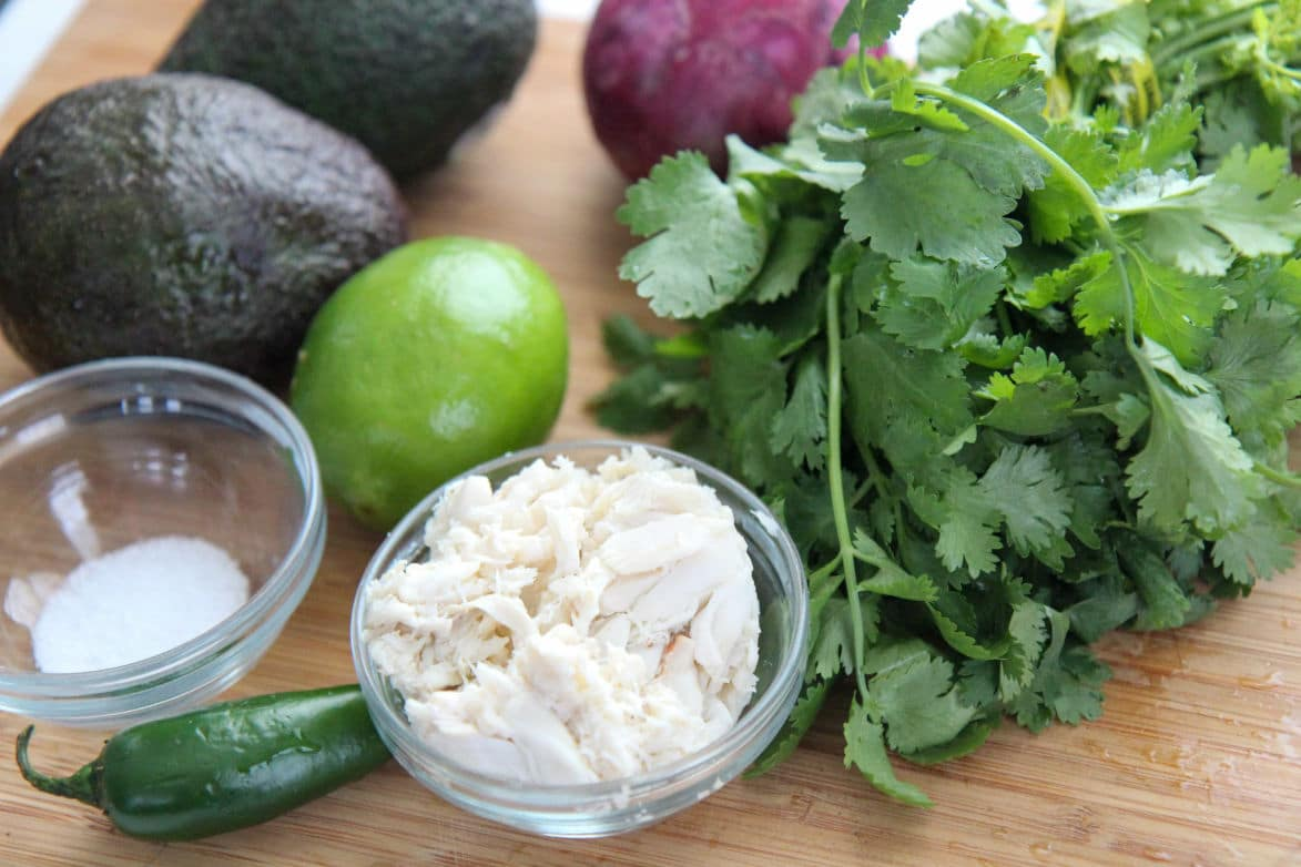 crab and salt in small bowls with cilantro, lime, avocados, and jalapeno