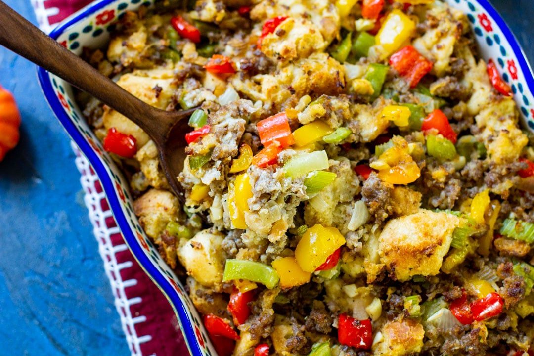 sausage stuffing in a casserole with a wooden spoon