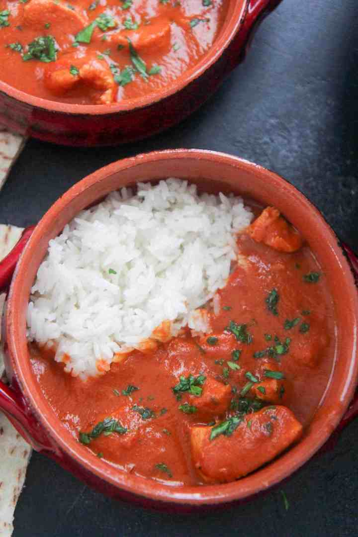 small red bowls with butter chicken and rice
