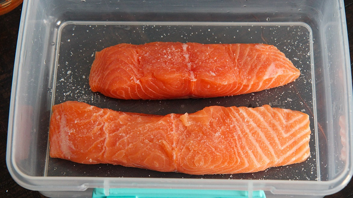 seasoned salmon in a plastic container