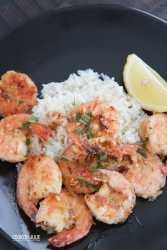 Hawaiian garlic shrimp, white rice, and lemon on a black plate