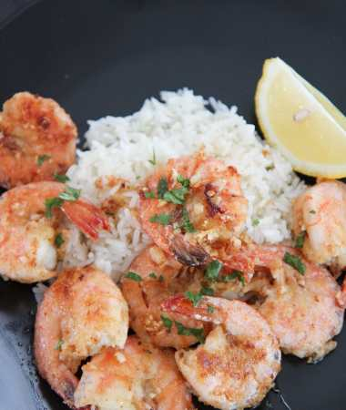 Hawaiian garlic shrimp, white rice, and lemon on a black plate