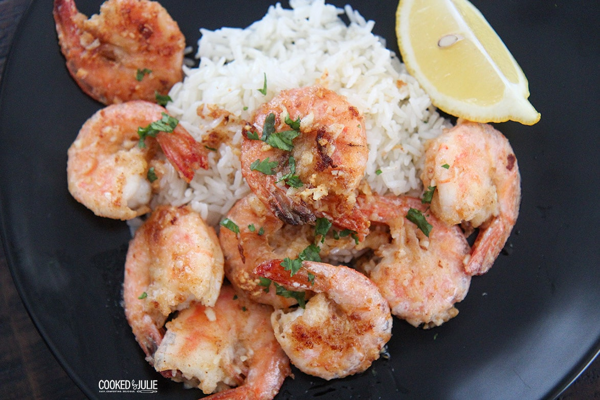shrimp and rice on a dark plate with a lemon wedge