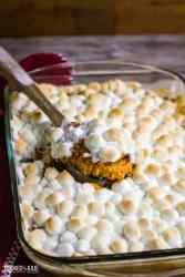sweet potato casserole in a baking dish with wooden spoon