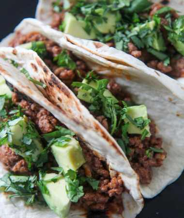 three Cajun beef tacos on a black plate