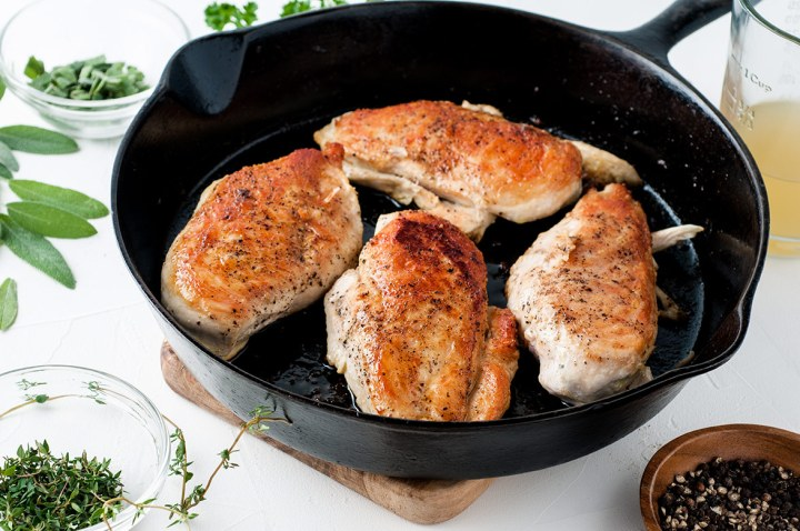 four cooked chicken breasts in an iron skillet