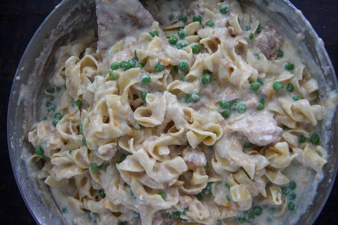 cream sauce, egg noodles, peas, and tuna in a skillet
