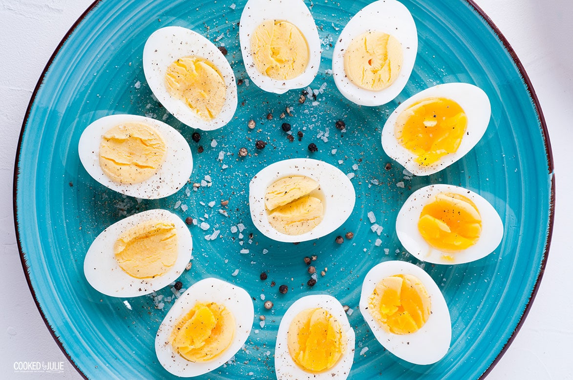 sliced soft and hard cooked eggs arranged in a flower patter and sprinkled with salt and pepper on a teal plate