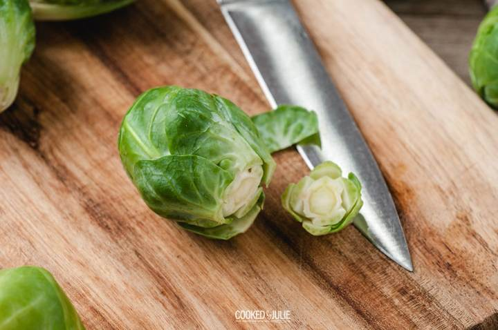 brussel sprouts on a wooden board with a knife