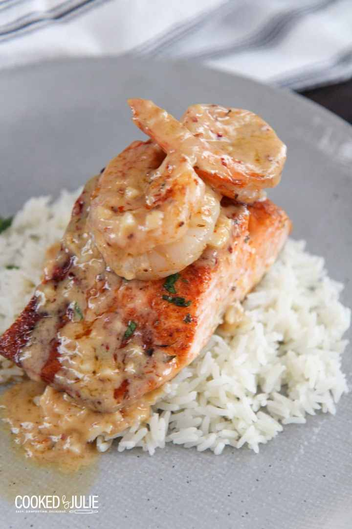 salmon and shrimp over white rice on a plate