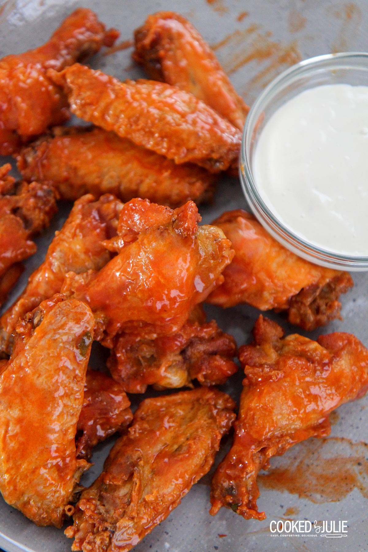 baked buffalo wings on a gray plate with a side of bleu cheese