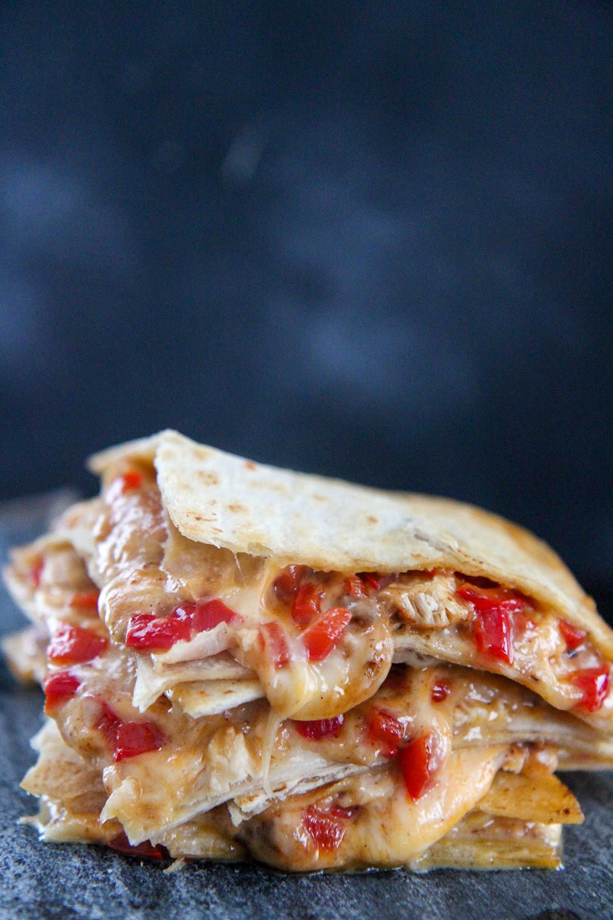 four cheesy chicken quesadillas stacked up close