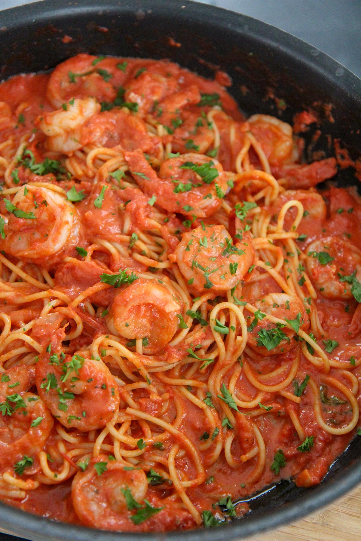 creamy spicy shrimp spaghetti with parsley in a black skillet