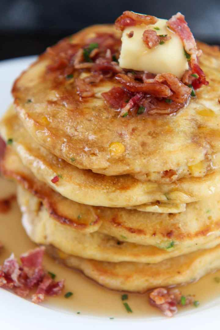 pancakes with a slice of butter and crispy bacon on top up close.