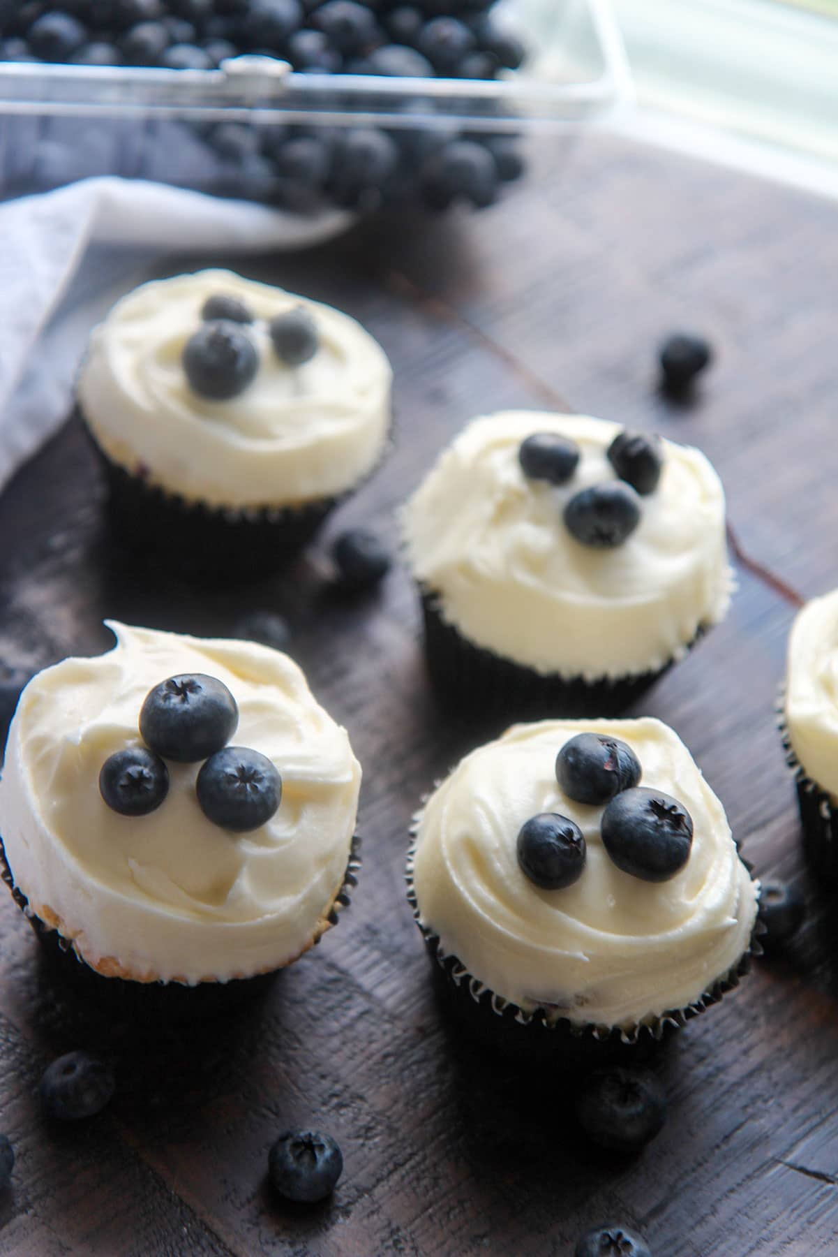 four cupcakes and fresh blueberries on the side