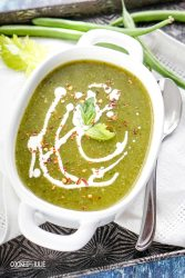 vegan green detox soup with cream in a white bowl