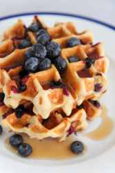 two buttermilk blueberry waffles on a white plate with maple syrup and fresh blueberries.
