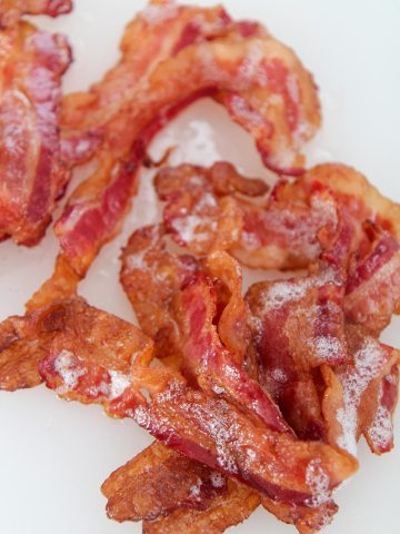 one pound of crispy bacon up close on a white chopping board.