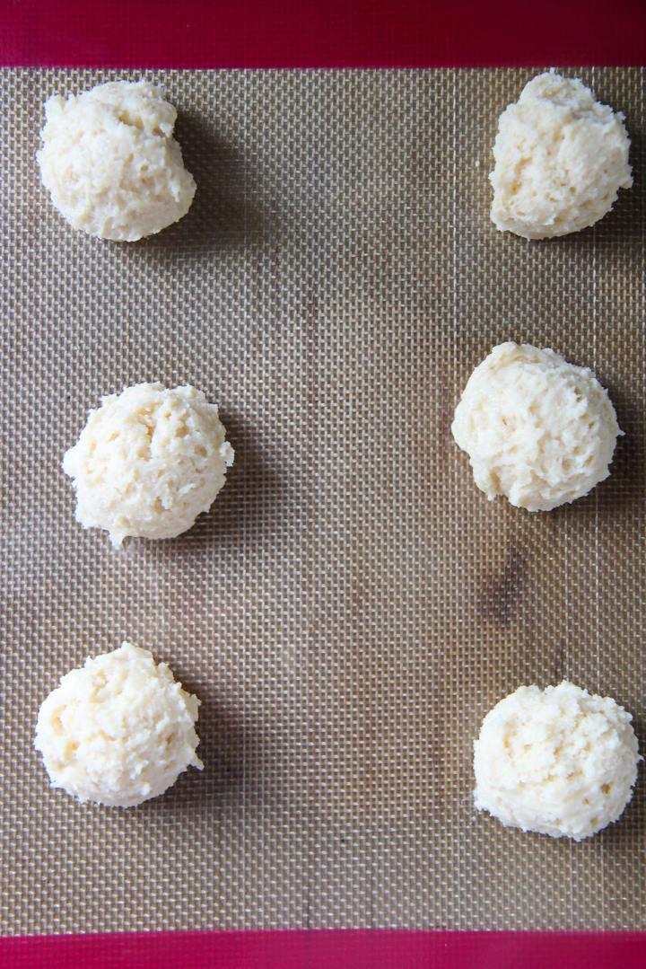 six cookie dough balls on a baking sheet.