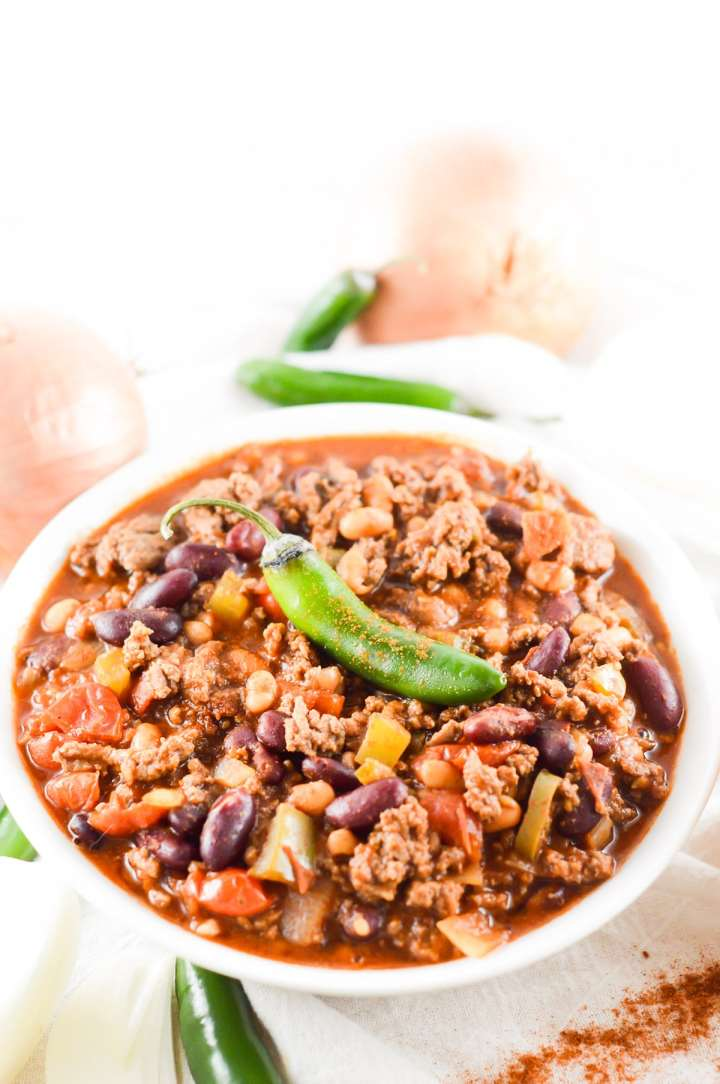 crockpot chili in a white bowl with fresh jalapeno on top and onions on the side.