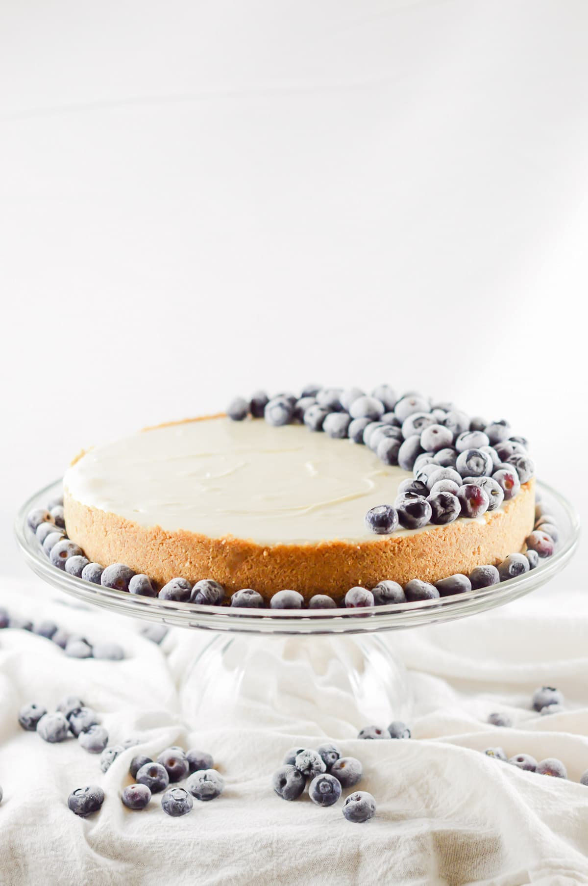 a whole plain no bake cheesecake on a cake stand decorated with fresh blueberries.