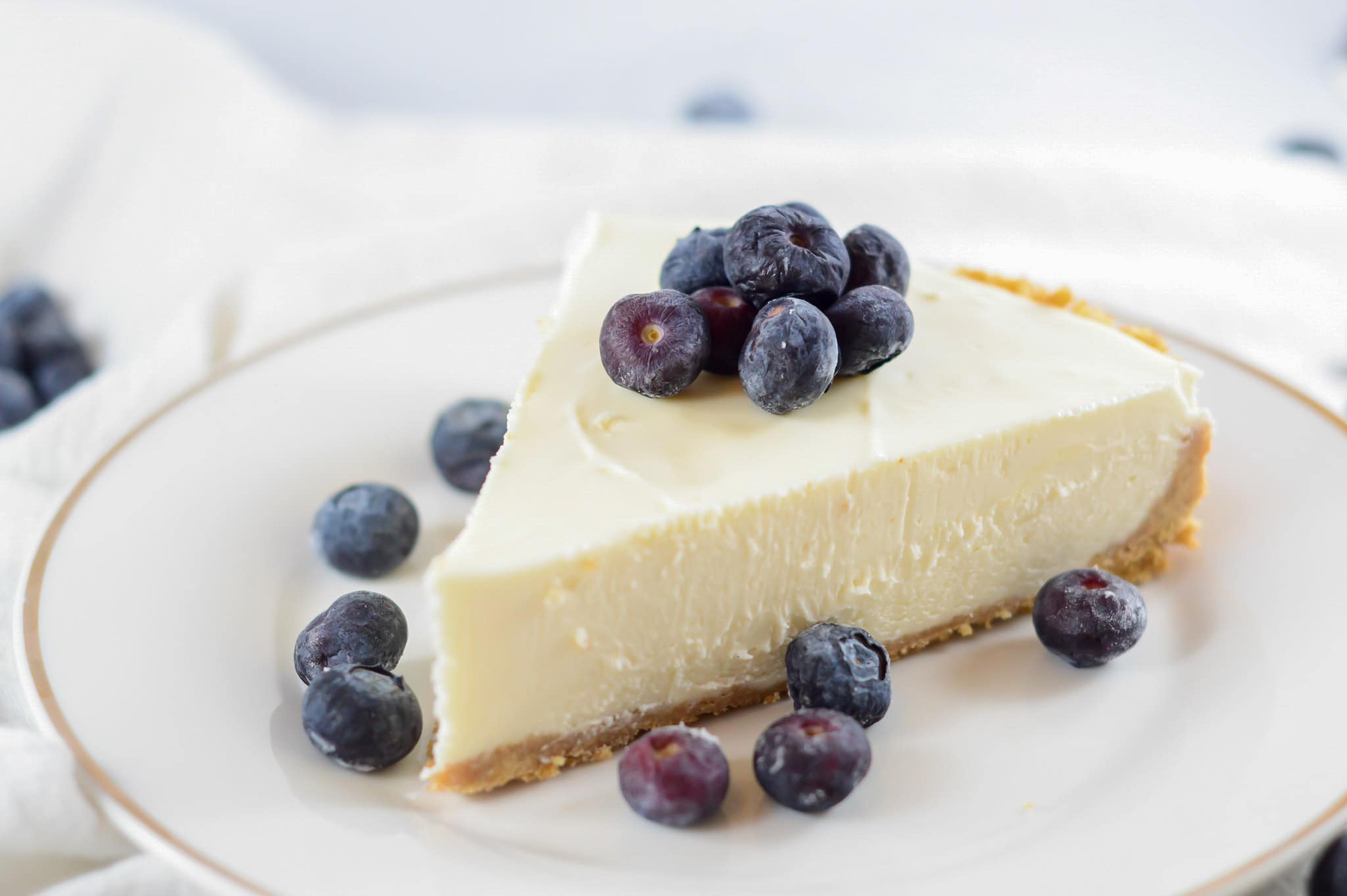 a slice of no-bake cheesecake on a white plate with fresh blueberries.