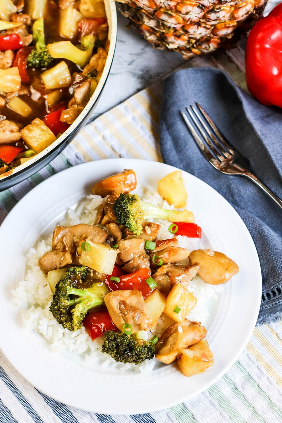 pineapple chicken stir-fry over white rice on a white plate with a fork on the side and skillet in the background.