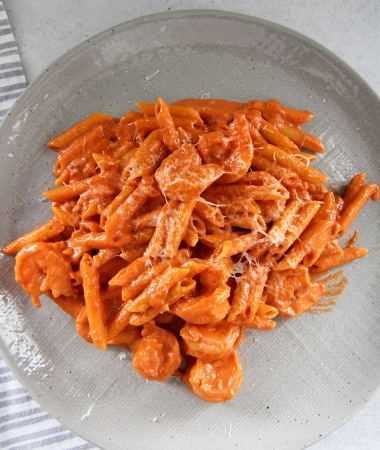 penne alla vodka with shrimp on a gray plate with a gray and white towel on the side.
