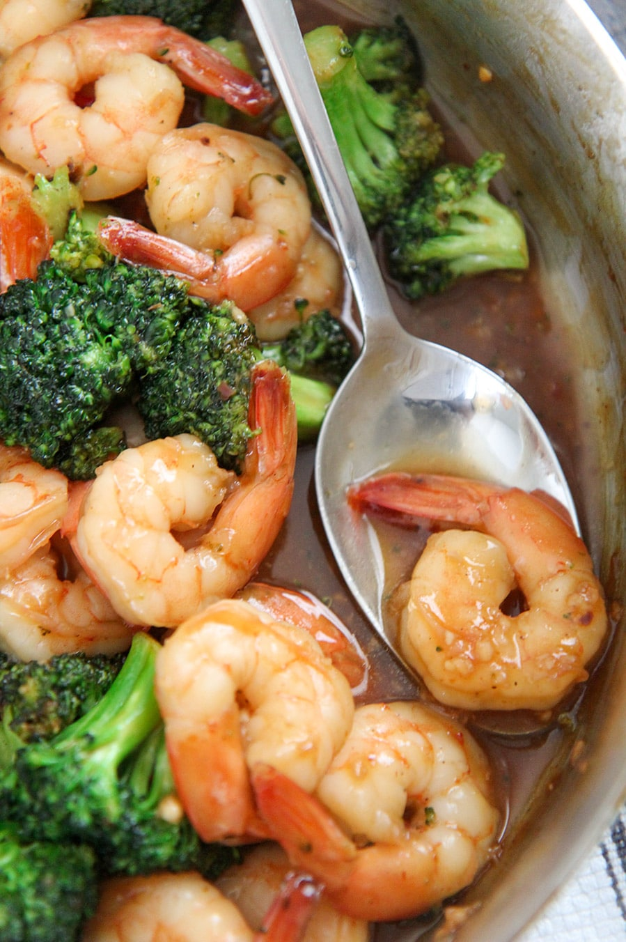 spicy honey shrimp and broccoli in a skillet with a spoon holding one shrimp.